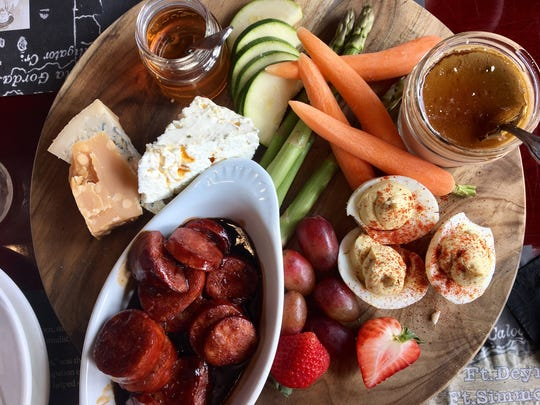 A tasting board with wine-poached andouille, cheese,