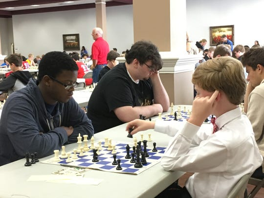 Center Hill High School student William Wright (left) makes a move against Canaan D. Milligan, who attends Olive Branch High School. Sitting next to him his teammate Daniel Bedrossian plans his next move at the 2016 DeSoto County School Chess Championship.