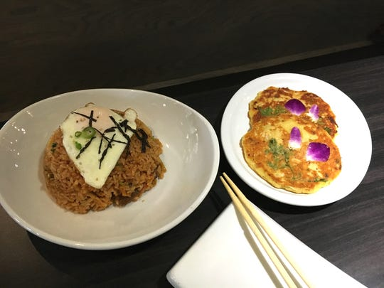 At Janchi Korean BBQ in Thousand Oaks, an order of kimchi fried rice comes with an egg on top, left, while myung bean pancakes are decorated with herbs and orchid petals cooked into the batter.