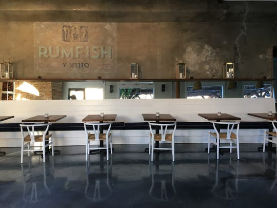 Mirrors, white chairs and a refinished concrete floor are part of the decor at Rumfish y Vino, now open in The Livery complex in downtown Ventura.