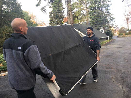 Keith Kazmark, mayor of Woodland Park, and Mohamed Khairulluah, mayor of Prospect Park, carry out donations of furniture to be given to three Syrian refugee families from a home in Little Falls on Saturday, Nov. 26, 2016.