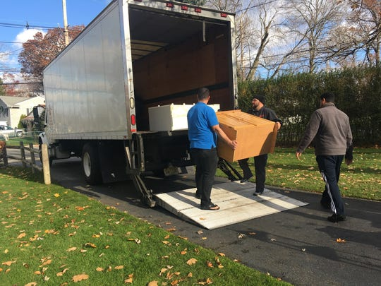 Volunteers collect donations of furniture for three Syrian refugee families from a home in Little Falls on Saturday, Nov. 26, 2016.