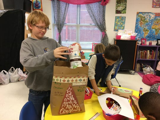 Adam Rowe adds a small blanket to the gift bag he is working on while Taylor Cook continues to decorate the gift bag he will fill.