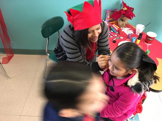 Saida Ochoa gets a snowman on her cheek from a face painting elf at the Sierra Vista Primary school breakfast with Santa event Saturday.