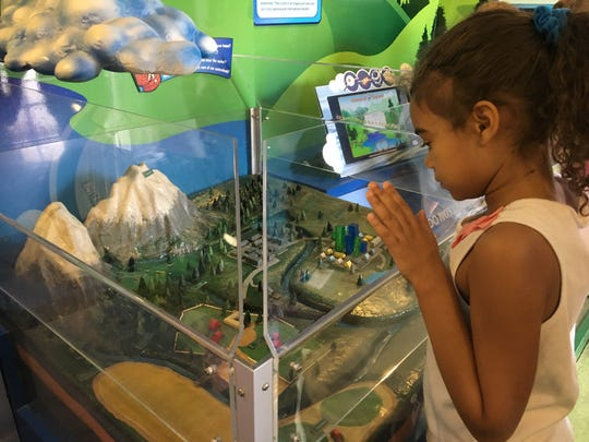 Jade Robertson, 8, peers into a watershed display that showed what happens to rain after it falls onto Earth.