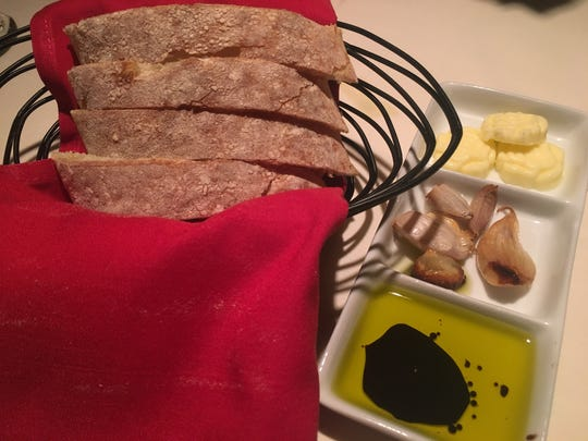 Complimentary bread is served warm alongside an attractive presentation of butter, roasted garlic and olive and oil and balsamic vinegar.