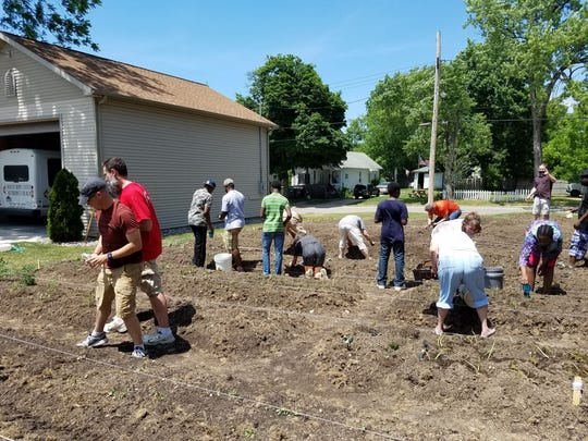 U.S. and foreign-born volunteers work last summer in the vegetable garden they share alongside the garage at Mount Hope United Methodist Church in Lansing. More than a quarter of the church's members are refugees or immigrants, according to pastor Rob Cook.
