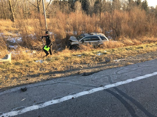 Trooper Duane Hunsicker with the Ohio Highway Patrol takes measurements of the scene after a crash at Ohio 13 and Ohio 96 on Thursday. One woman was injured in the two-vehicle crash.