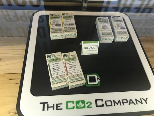 """A """"sold out"""" sign sits among CO2 marijuana products at TLC Cannabis Emporium in Salem, Ore., on Dec. 19, 2016."""