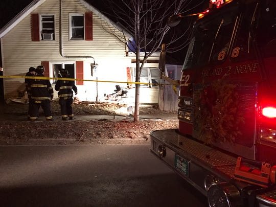 Burlington firefighters respond after a car hit a house Monday evening, Dec. 26, 2016, in the city's Old North End.