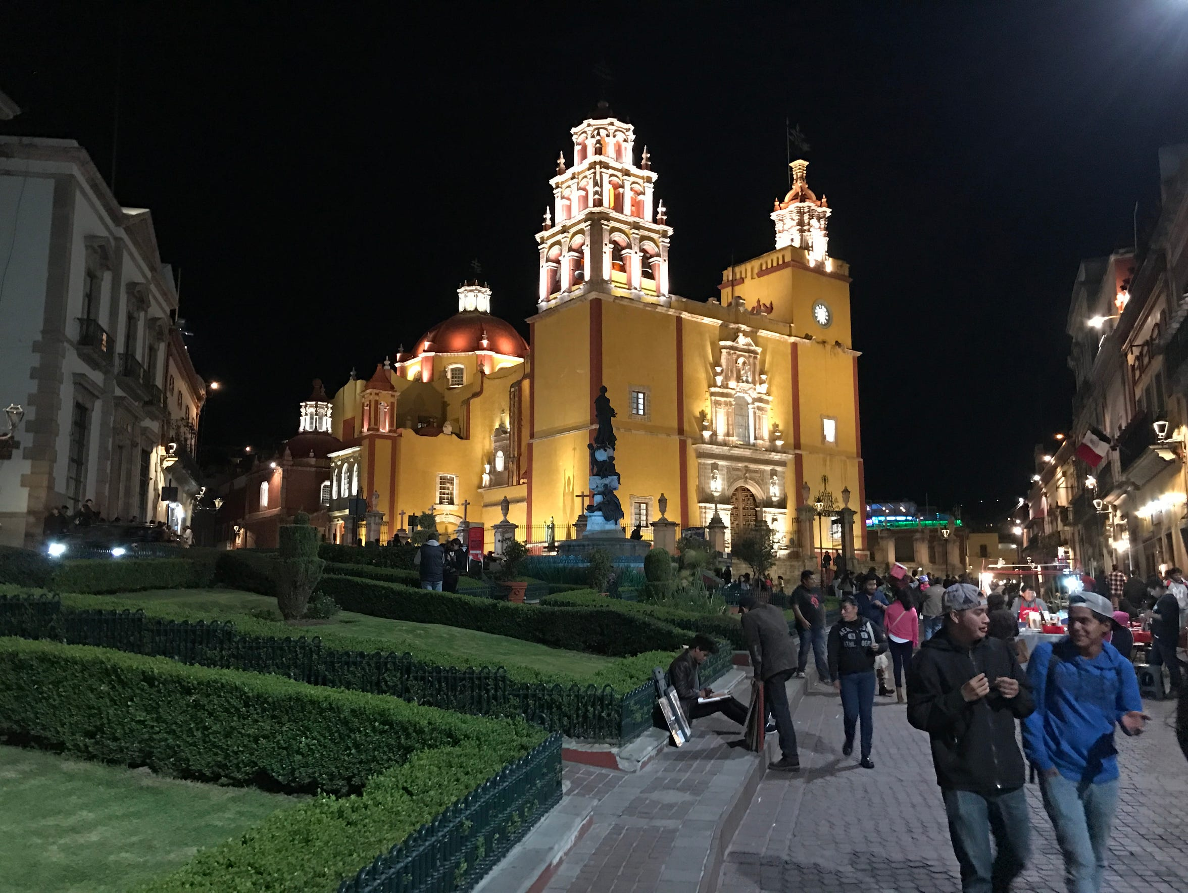 People walk by a church awash in lights in Guanajuato.