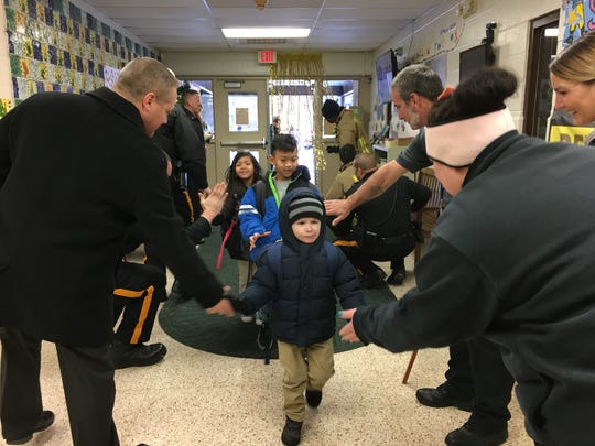 Students at Winslow School No. 1 are greeted by police, fire and EMS high-fives to kick off the school's weeklong Great Kindness Challenge.