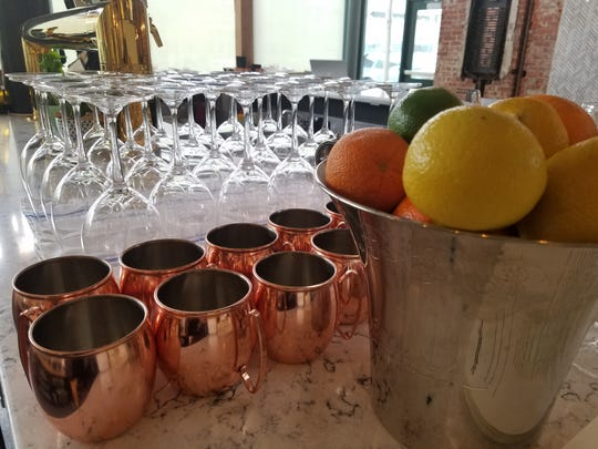 Moscow mule cups, wine glasses and fresh citrus stand ready behind the bar at The Garden Table, 342 Massachusetts Ave.