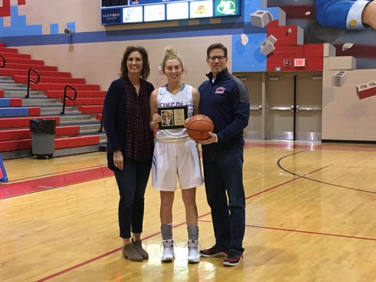 Anna Brecht poses with her parents, Amy Mickelson Brecht and Jeff Brecht after breaking Sioux Falls Lincoln's career scoring record on Tues., Jan. 10, 2017 against Yankton.