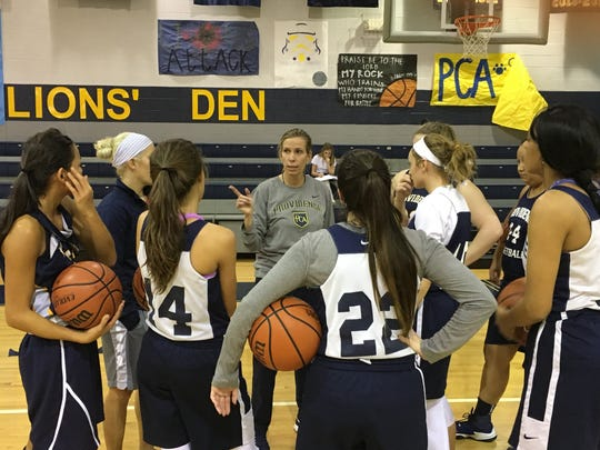 Providence Christian Academy players huddle around Coach Tara James during a practice this past season.