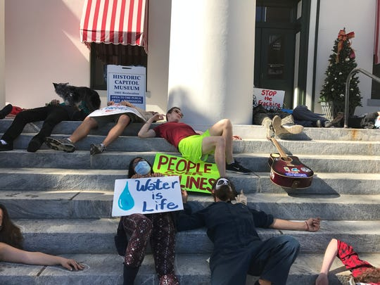 "Protesters pretend to be dead at  a ""Die-in"" on steps of the Old Capitol Thursday."