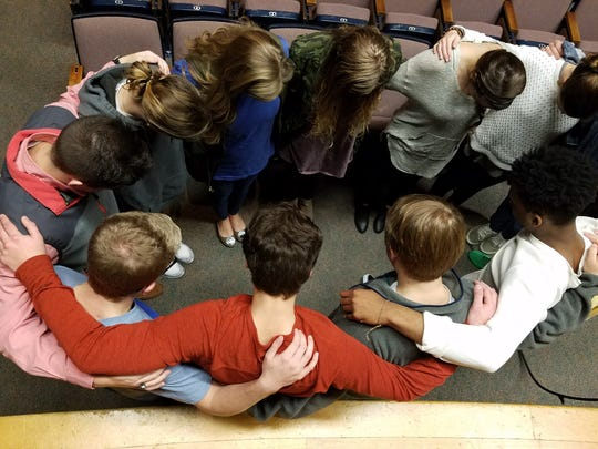 The leadership teams for The Chill pray together before going to class after the service Friday morning.