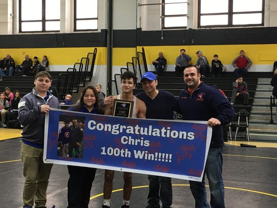Chris Caban, center, celebrates after his 100th career victory.