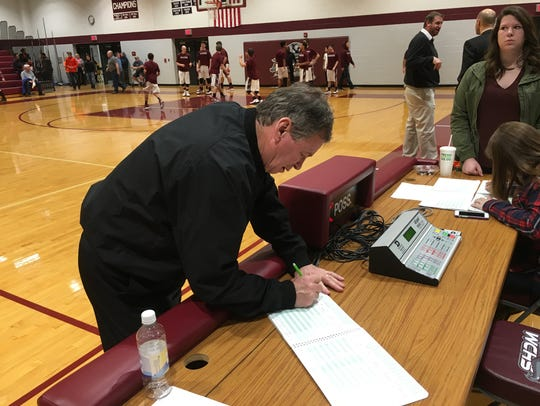 Mike Ruckman, Sr. signs the scorebook before the start