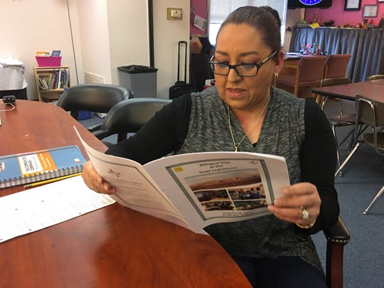 The Ruidoso school district's bilingual program coordinator reviews award citations for three local schools that took 3 of the states 10 awards for bilingual multicultural programs.