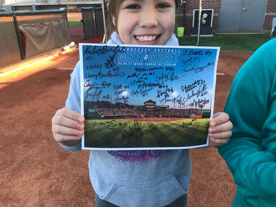 """Mackenzy Navarro, 10, holds up the placard she had players autograph at the Tennessee softball """"Meet and Greet"""" on Saturday."""