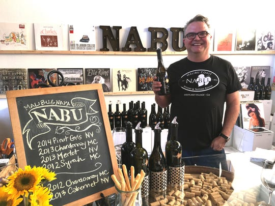 Greg Barnett of NABU Wines poses with a bottle of Malibu Coast syrah in the label's Thousand Oaks tasting room in 2016. Named for its use of grapes from Napa Valley and Malibu, NABU is one of five Conejo Valley wineries participating in Wine N Roses, a Valentine's Day-themed promotion.