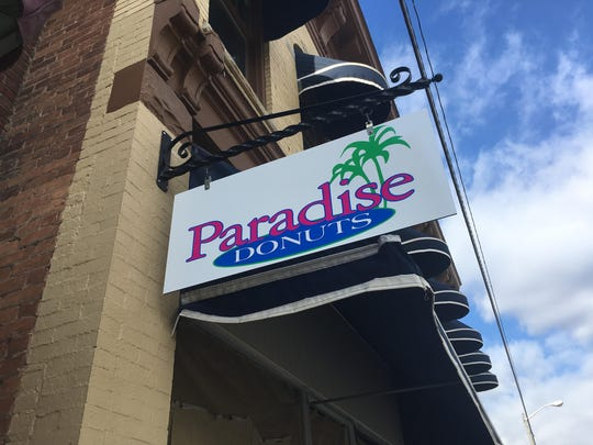 A Paradise Donuts sign hangs outside a storefront on