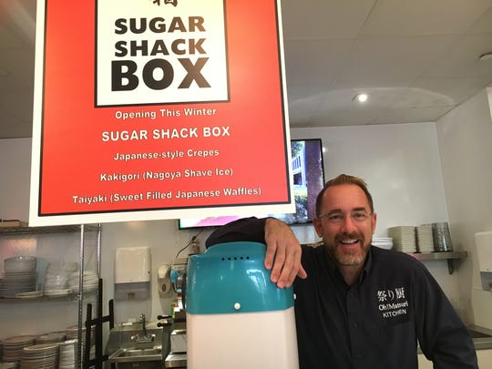 Gordon Hardey, owner of Jeannine's Gourmet Food Hall in Westlake Village, poses with a sign touting the Sugar Shack Box counter he plans to unveil at the Shoppes at Westlake Village site later this month.
