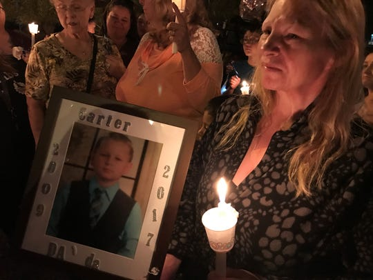 Mesa resident Debora Wickland holds a photo of 7-year-old