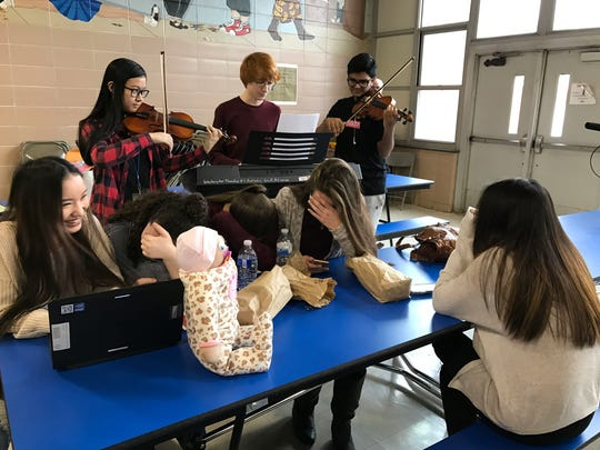 Washington Township High School junior Michelle Le (right) and her friends (from left) Sophia Paredes, Lilly Torres, Julia Hancock and Jenny Kerrigan, giggle as a chamber orchestra trio serenades Le on Valentine's Day.