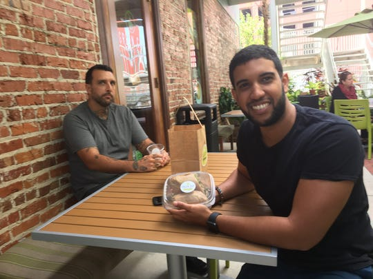 From left to right: Millennials Cory Patterson and K.J. Adames enjoy lunch at the Green Cup Cafe Wednesday.