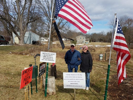 Jim and Sharon Girvan on the front lawn of their Branchburg home with some of their signs against the Trump Administration and an upside-down American flag, a symbol of distress.