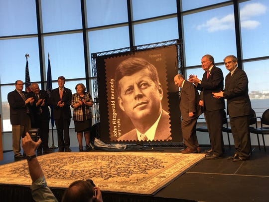 The unveiling of the President John F. Kennedy  commemorative stamp in Boston Monday. Photographer Ted Spiegel, of Fishkill, is to immediate right of stamp. Also present was Postmaster General Megan Brennan to the left of the stamp.