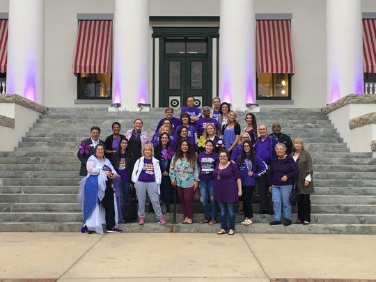 Alzheimer's advocates from Southeast Florida stand on the steps of the Old Capitol after it was turned purple for Alzheimer's awareness.