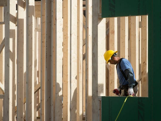 A construction worker installs wall sheathing on one