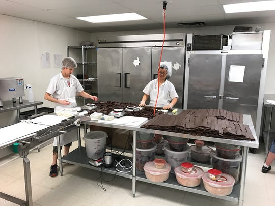 Workers produce meat and vegetable bars in the downtown Loveland Wild Zora kitchen.