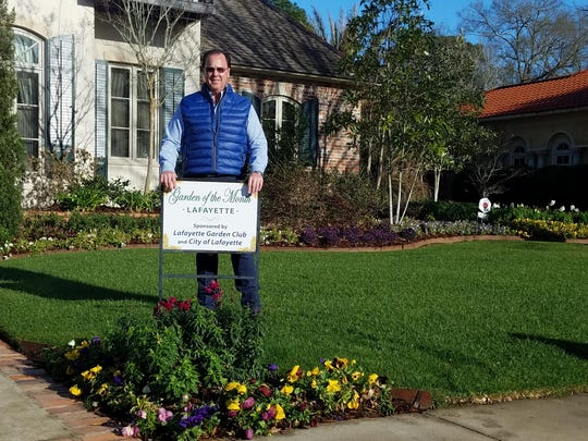 The Lafayette Garden Club has presented the Garden of the Month award for March 2017 to Mr. and Mrs. Aubrey Cole of 101 Riverbriar Road.   The lovely garden beds are currently in bloom with white and red snapdragons, white, yellow, purple and lavender pansies as well as beautiful red camellias. Trees planted throughout the landscape are magnolia, crepe myrtle, palm and cypress, and a lovely live oak surrounded by a planting of vibrant green hosta and lavender pansies. Other accent plants are ornamental cabbage, agapanthus, foxtail fern, loropetalum, mini bottle brush and pampas grass. Shown accepting the award is Aubrey Cole.