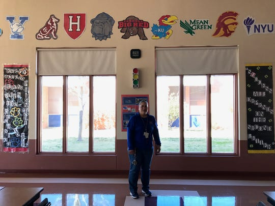 Annette Payan stands in front of her college logos, which she draws using a projector, markers and paint.