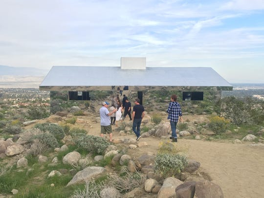 """Visitors head to """"Mirage,"""" by artist Doug Aitken on Saturday, the first day of Desert X. The piece is a ranch-style home made entirely of mirrors. Aitken says the piece """"distills the recognizable and repetitious suburban home into the essence of its lines, reflecting and disappearing into the vast western landscape."""""""