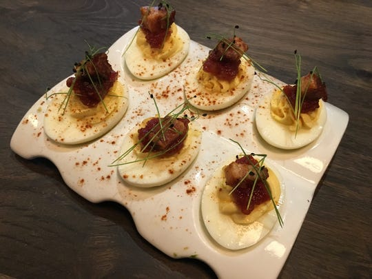 The bacon & eggs, deviled stuffed eggs, tomato jam and candied bacon, are on the appetizer menu for $7.