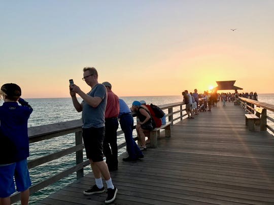 Tourists taking photos of the dolphins at Sunset on Naples Pier.