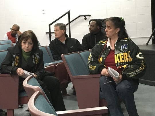 Ellen Tucker (left) and Debra Kessel listen at a meeting of where St. Francis residents voice concern over the smoke coming from a nearby barrel refurbishing plant.