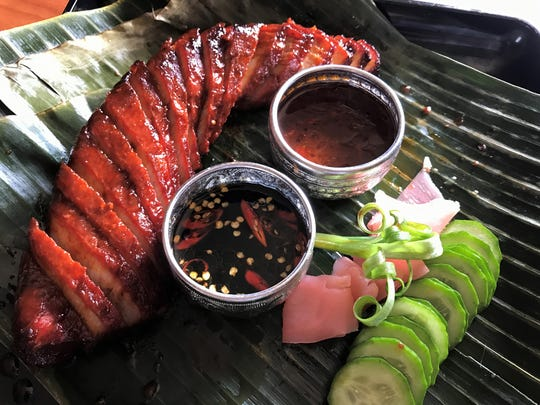 Thai roasted red pork is a delicacy served on banana