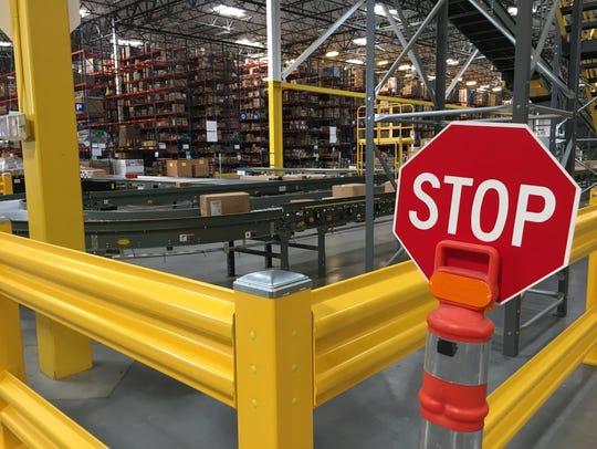 A conveyor carries merchandise across the massive warehouse