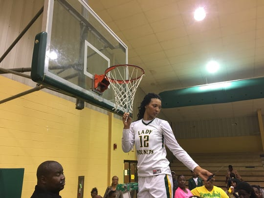 "Rayville's Micaela Wilson cuts down the nets inside the Hornet's Nest after advancing to ""Marsh Madness."""