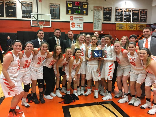 The Somerville girls basketball team celebrates its first sectional title since 1985 after topping Voorhees 80-60 Tuesday evening