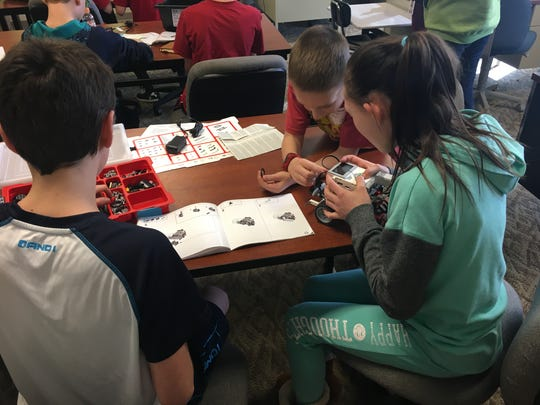 Team Sleep, made up of James Meece (left), Ayana Pender (right), and Joshua Tenbarge work on their LEGO robot Wednesday morning. About 15 EVSC Virtual Academy students in first through eighth grades have worked on the robots weekly for about a month.