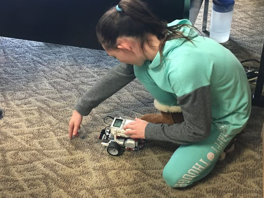 Ayana Pender tests Team Sleeps' LEGO robot Wednesday morning. About 15 EVSC Virtual Academy students in first through eighth grades have worked on the robots weekly for about a month.