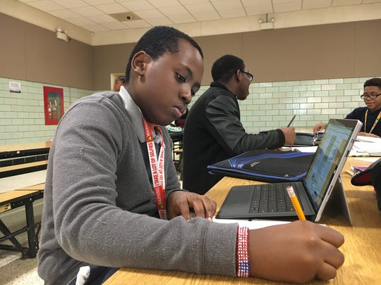 Nathan Wachira, a seventh-grader, works on  an essay during an after-school program at Kirk Middle School run by 4-H.