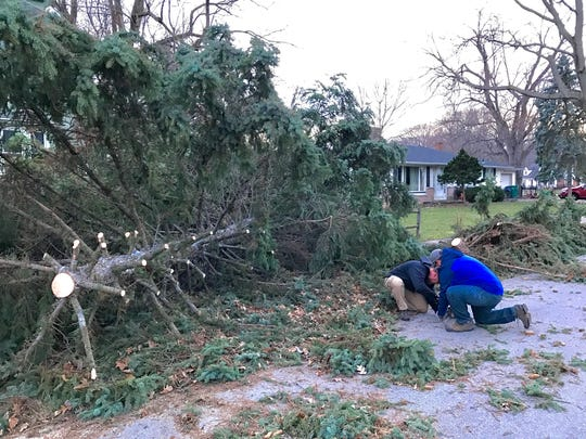 Matt Cleckner and Paul Dill help remove downed trees from their Irondequoit neighborhood.